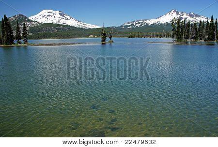 two volcanoes rise beyond a mountain lake