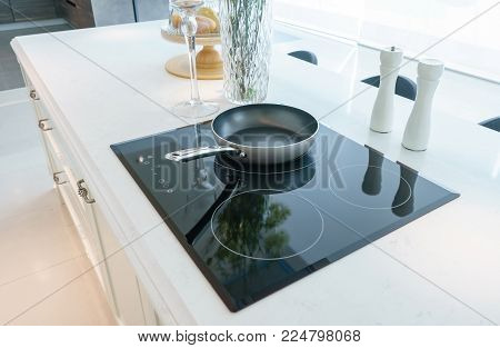 Frying pan on modern black induction stove, cooker, hob or built in cooktop with ceramic top in white kitchen interior poster