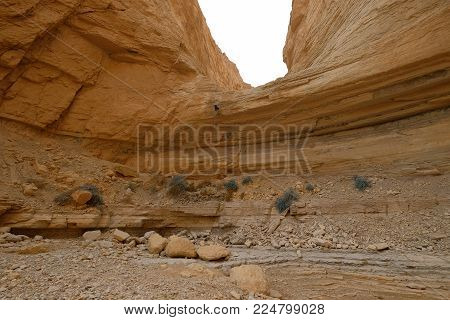 Climber abseiling down from rock cliff in dry wadi in Judea desert.