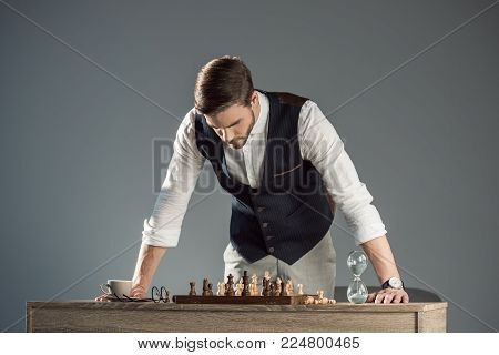 focused bearded stylish man looking at chess board with figures