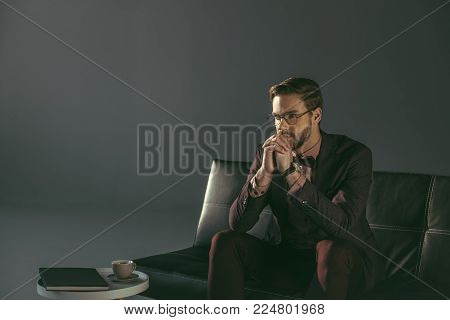 pensive young stylish man in eyeglasses sitting on couch and looking away