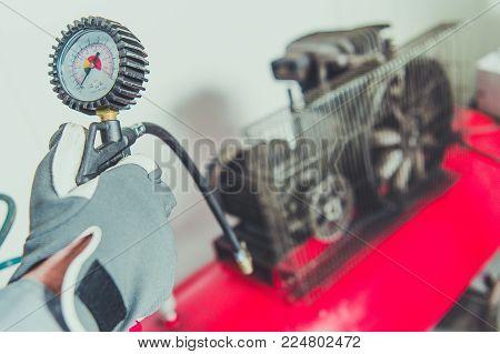 Worker Using Air Compressor Tool. PSI Meter Closeup. Air Pressure Generator Equipment.