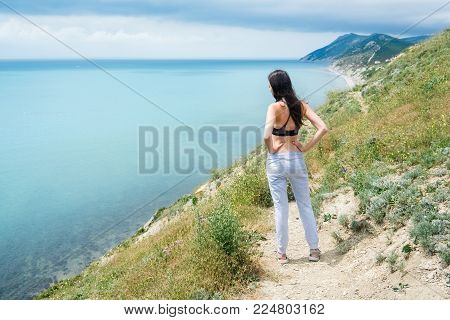 Young woman of 25-30 years worth of grief and looks at sea, back view. Dressed in pants and top.