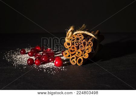Cranberries in sugar and cinnamon sticks. Cranberries and cinnamon on a black background. Directly above.