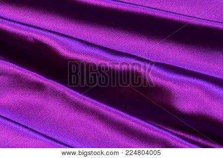 Beautiful closeup of gathered stripes of ultra violet purple bridesmaid gown prom dress; dressy fancy soft satin fabric material