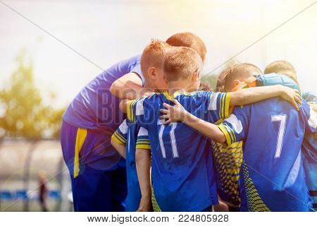 Kids sport team having pep talk with coach. Children soccer team motivated by trainer. Coaching football youth team. Young boys standing together united