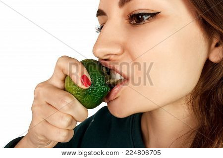 Young woman bite eat fresh lime isolated on a white background.