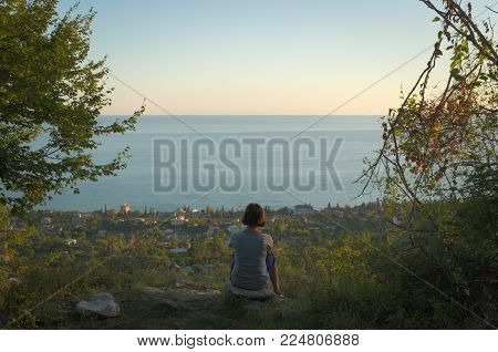 At sundown time a woman sits on a rock above a seaside town