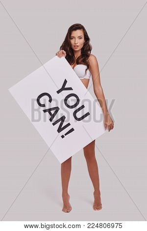 Everyone needs a bit of encouragement.  Full length of attractive young woman holding a poster and looking at camera while standing against grey background