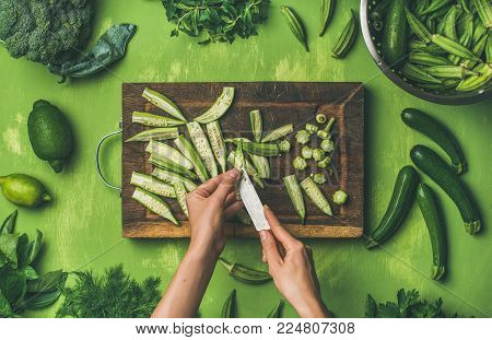 Healthy vegan cooking ingredients. Flay-lay of woman hands cutting green vegetables and greens over wooden green background, top view. Clean eating, vegetarian, detox, dieting food concept