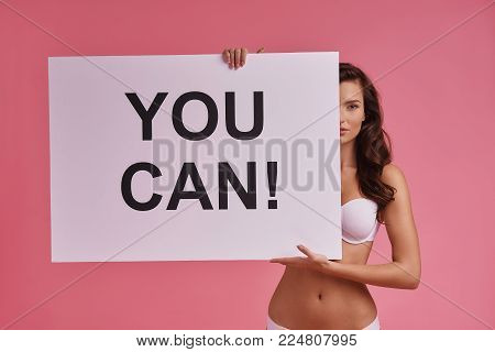 Encouraging others.  Attractive young woman covering a half of her face with poster and looking at camera while standing against pink background