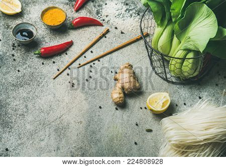 Asian cuisine ingredients over grey concrete background, copy space. Vegetables, spices, noodles, sauces for cooking vietnamese, thai or chinese food. Clean eating, veretarian food concept