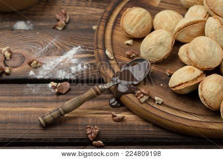 homemade cookies shaped nuts with cream boiled condensed milk on wooden table. Rustic style. spoon with condensed milk. scattered cleared nuts