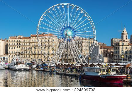 Marseille, France - December 4, 2016: Large Ferris wheel at square of Old Vieux Port of Marseille, Provence, France. Fish market on the shore.