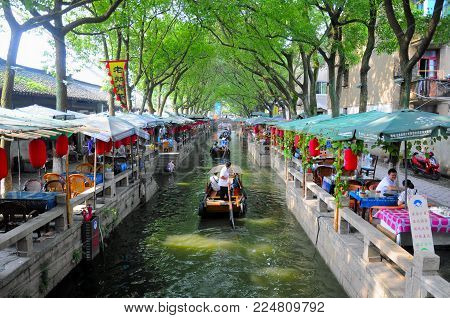 July 25, 2015. Tongli Town, China.  A tourist boat moving by a coffee house on the water canals within Tongli Town scenic area in Jiangsu Province China.