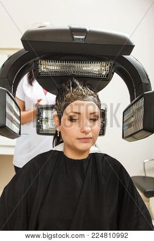 Haircare, relaxation and hairstyling concept. Woman sitting in black cape getting her hair dried under machine