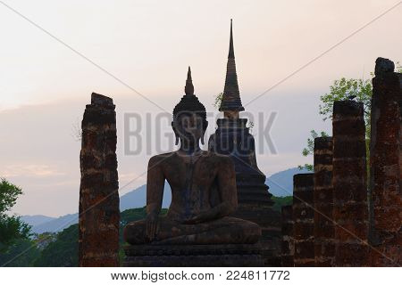 A statue of a seated Buddha on the ruins of the Wat Chana Songkram temple in the evening twilight. Sukhothai, Thailand