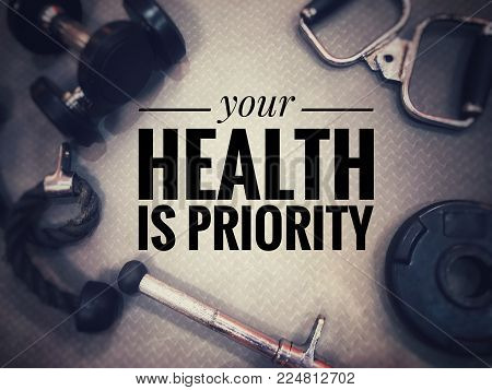 Motivational and inspirational fitness concept - Your health is priority with gym equipment as background. Blurred vintage style.