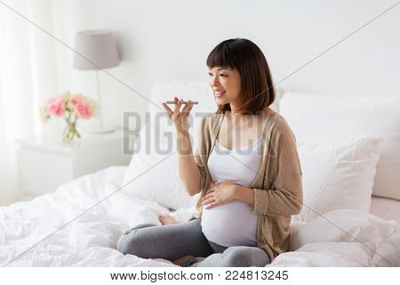 pregnancy, motherhood, technology, people and expectation concept - happy pregnant asian woman using voice command recorder or calling on smartphone at home