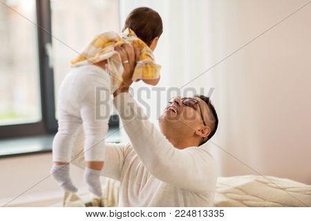 family, fatherhood and people concept - happy father holding little baby daugter at home