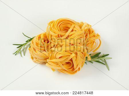 bundles of dried ribbon pasta on white background