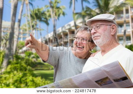 Happy Senior Adult Couple Tourists with Brochure Next To Tropical Hotel and Palm Trees.