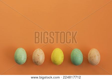Gold speckled Easter eggs arranged in a row on a bright orange background.