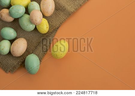 Gold speckled Easter eggs on a bright orange background with a burlap textile fabric.