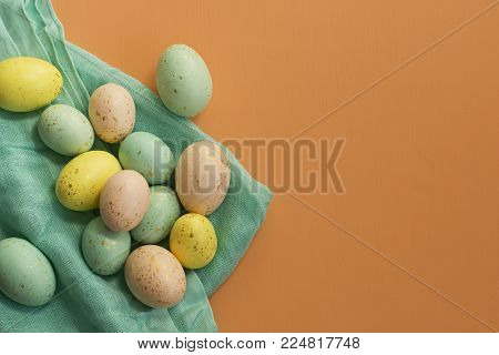 Gold speckled Easter eggs on teal fabric on a bright orange background.
