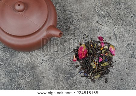 Teapot with tea and a pile of scented loose tea leaves and buds of dry flowers on a gray marble or concrete background (top view, flat lay), selective focus on the tea leaves