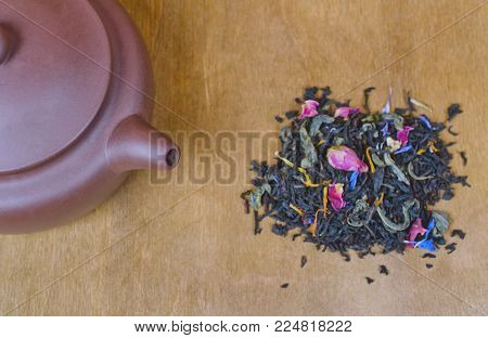Teapot with tea and a pile of scented loose tea leaves and buds of dry flowers on a wooden background (top view, flat lay), selective focus on the teapot