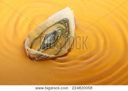 a paper boat from a hundred dollar bill on the surface of a liquid