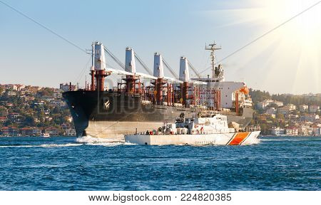 Coast guard vessel and Large cargo ship proceeding along the Bosphorus Channel on the background of the coast on the background