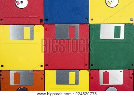 Horizontal close-up shot of nine multicolored plastic diskettes.  Shows fronts and backs of disks.