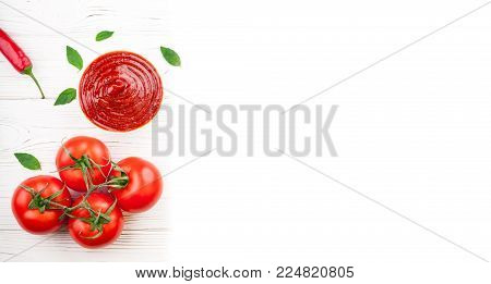 Tomato ketchup sauce in a bowl with chili, basilic and tomatoes. Ingredients for cooking  ketchup. Long format with copy space