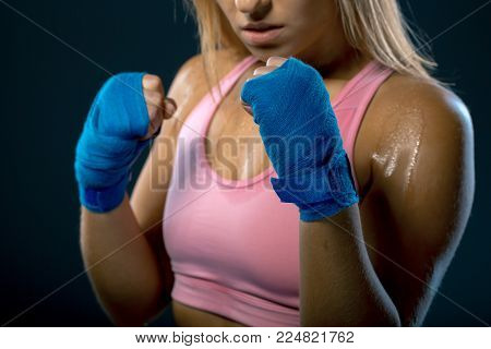 Boxing woman. Young woman fighter ready to fight. Strong woman. Female hands wrapped in boxing bandage over dark background