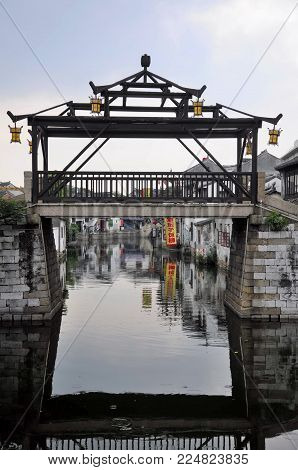 July 25, 2015.  Tongli Town, China.  A unique wooden bridge at the entrance intoTongli Town's Pearl Pagoda scenic area in Jiangsu Province China at dusk.