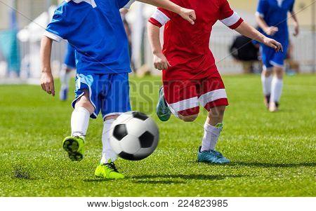 Soccer Kick; Running Soccer Football Players. Footballers Kicking Football Match; Young Soccer Players Running After the Ball. Footballers in Red and Blue Jersey Shirts Kicking Soccer Ball