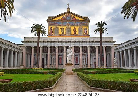 view of the statue of St. Paul and the main facade of papal Basilica of St. Paul outside the Walls in Rome, Italy