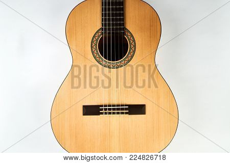 Acoustic guitar with nylon strings. Classical acoustic guitar isolated on a white background, close-up. Six stringed musical instrument