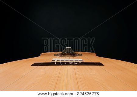Acoustic guitar with nylon strings, close-up. Classical acoustic guitar isolated on a black background with copy space. Six stringed musical instrument