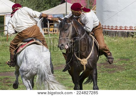 Almaty, Kazakhstan - August 23, 2015: Kazakh Men Do Traditional Nomadic Arm Wrestling On Their Horse