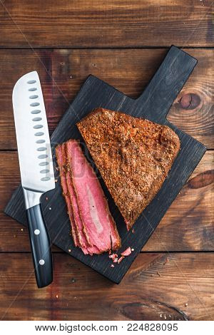 Deli Beef pastrami sliced on wooden board with knife, top view