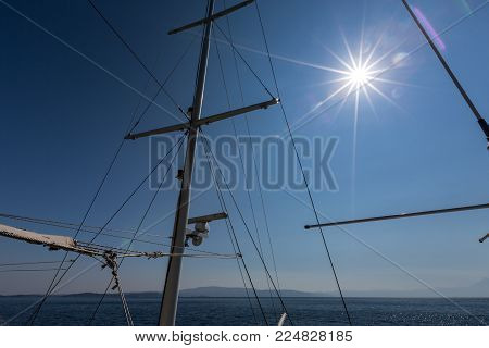 Mast and riggings of tourist ship in Greece over blue sky with Sun flares