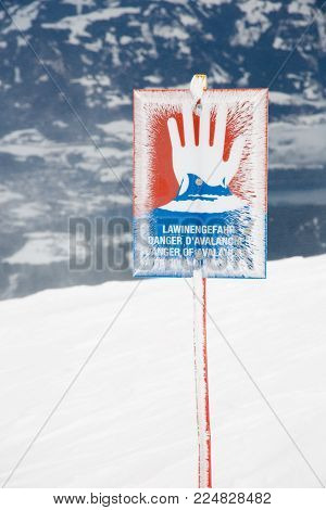 Danger sign remind the avalanche risk at the top of a snow covered mountain, next to the ski slopes.
