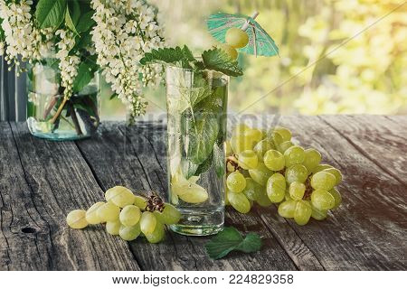 Detox water mint, grape juice and ice in a glass on a background of a bouquet of cherry and grapes in a Sunny day. The horizontal frame.