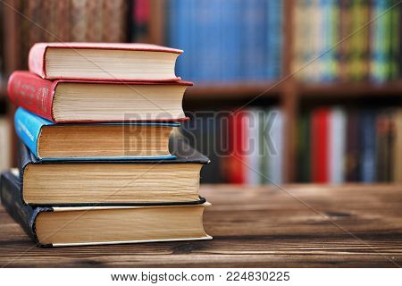 a stack of old paper books on a wooden table. Bookshelves in the background. Blurred background. horizontal photo