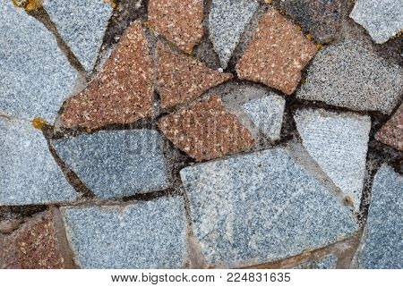 A large wall of natural granite stones of different size and color, a gray texture on a summer day, mosaic, stone fence, natural stone, granite multicolored, pattern blue brown red multicolored
