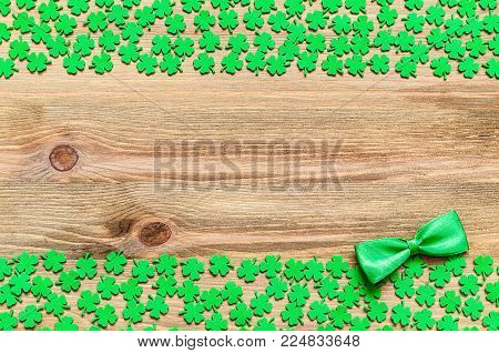 St Patrick's Day background. Green quatrefoils and bow tie on the wooden background, free space for St Patrick's day festive text message. Happy St Patrick's day concept