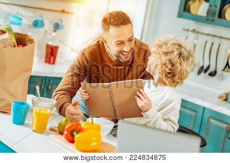 Book with recipes. Positive nice cute boy holding a notebook and looking at his father while choosing a recipe